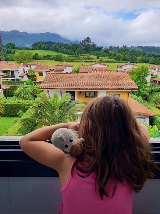 Vue d'une enfant et son toutou sur Colunga à partir d'une fenêtre